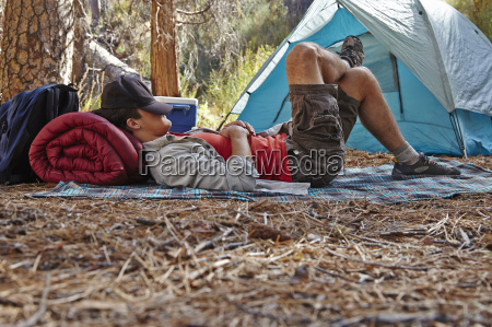 young, male, camper, resting, in, forest, - 18861558