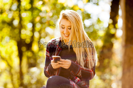 young woman reading smartphone text in