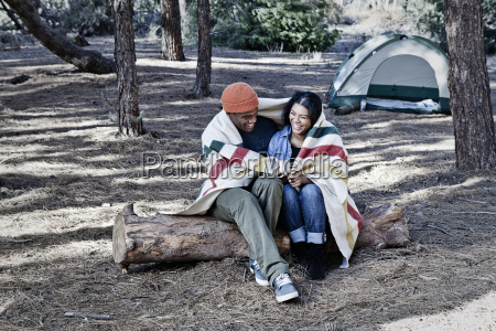 young camping couple sitting on log