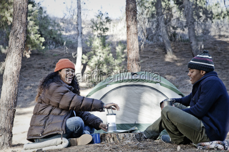 young camping couple sitting in forest