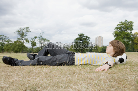 teenage boy resting on football