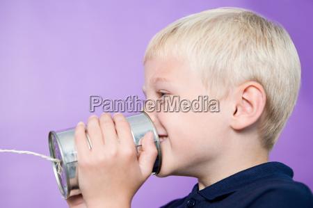 boy talking on a tin can
