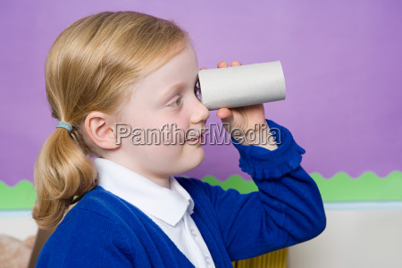 girl looking through toilet roll