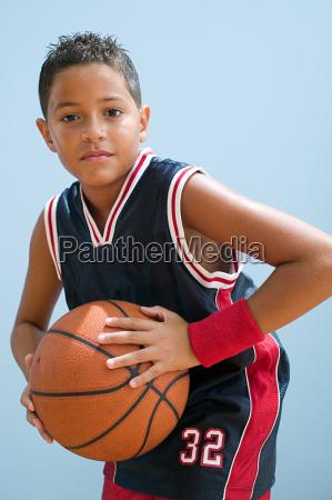 boy in basketball uniform holding basketball