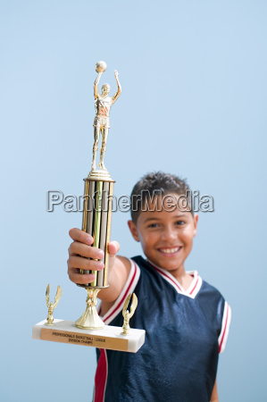boy holding up basketball trophy