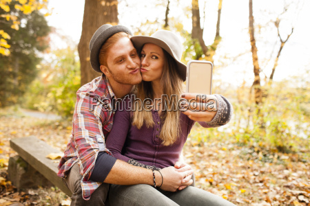 young couple on bench taking smartphone