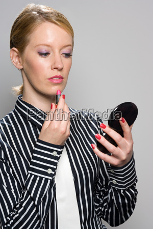 businesswoman applying lipstick