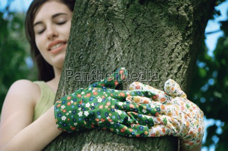 girl hugging tree trunk