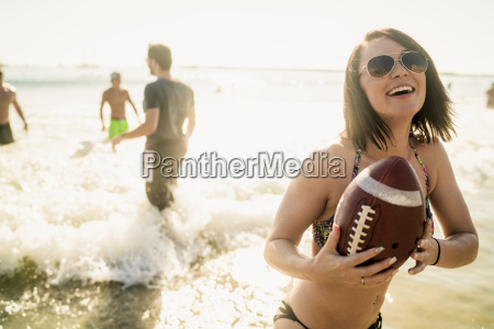young woman playing american football with