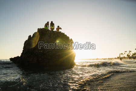 silhouette of adult friends on rock