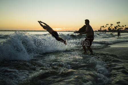 young men diving into sea at