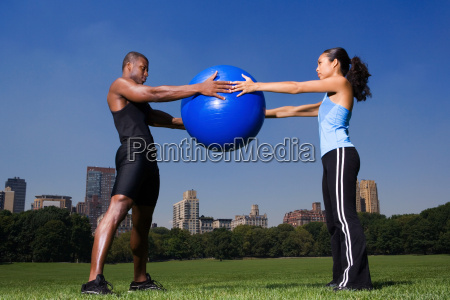 man and woman holding exercise ball