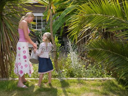 mother and daughter watering garden