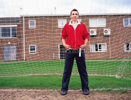 teenage boy standing in goal