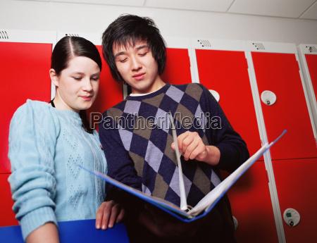 boy and girl looking at folder