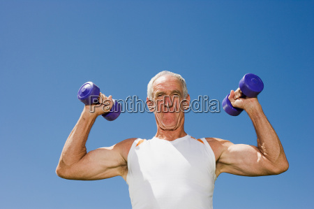 senior adult man lifting dumbells