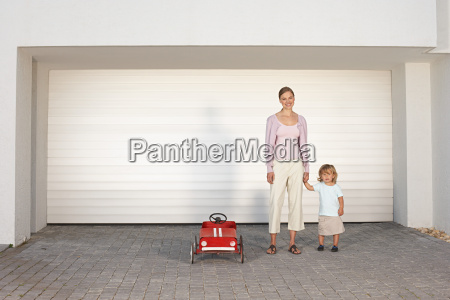 mother and daughter stood in driveway