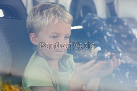 boy sat in car holding toy