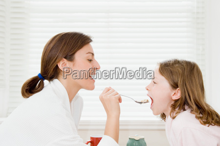 mother feeding daughter breakfast