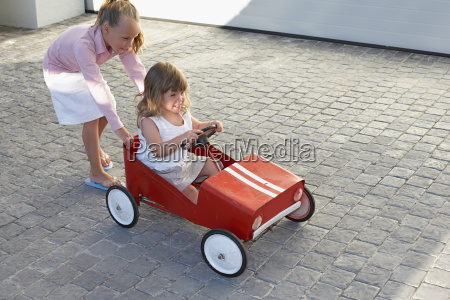 sister pushing her younger sister in