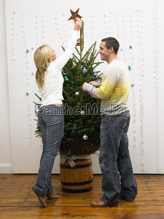 mid adult couple decorating christmas tree