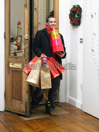 man returning home from christmas shopping