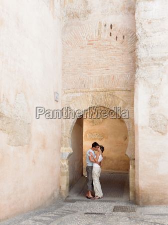 couple kissing under arch