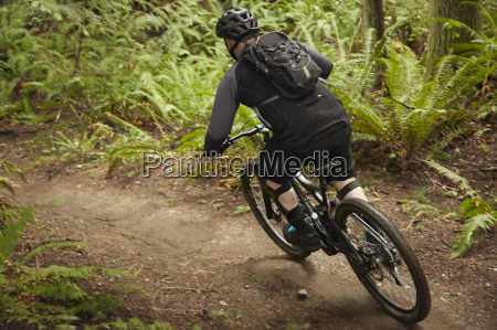 mature man riding mountain bike in