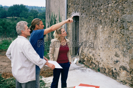 people looking at house wall