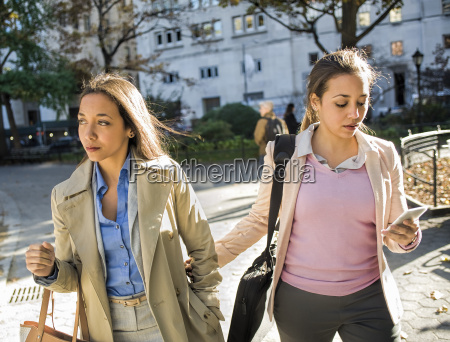 young adult female twins walking arm