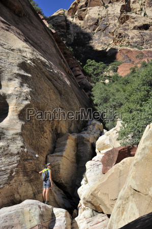 young female rock climber standing on