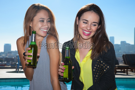 two young adult female friends drinking