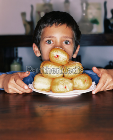 boy with plate of doughnuts
