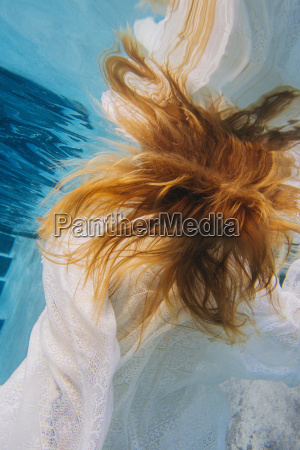 young red headed woman underwater overhead