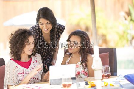 three adult sisters browsing digital tablet