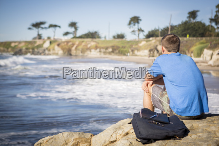 young man sitting by rock looking
