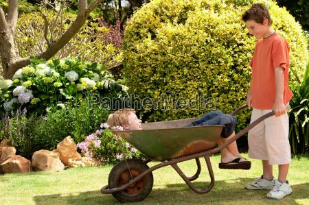 boy in wheelbarrow and friend