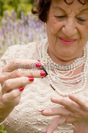 a senior woman applying nail varnish