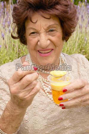 a senior woman holding a dessert