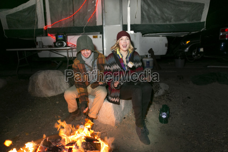 young couple sitting by camp fire