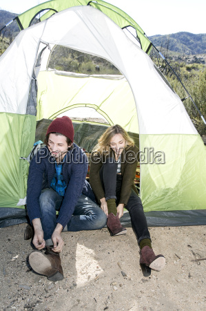 young couple sitting half in tent