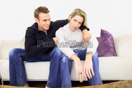man comforting friend on sofa
