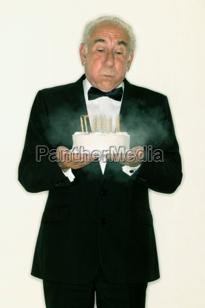 senior man holding a birthday cake