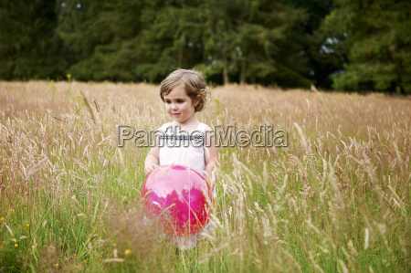 girl in tall grass holding red