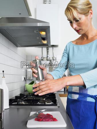 woman preparing steak