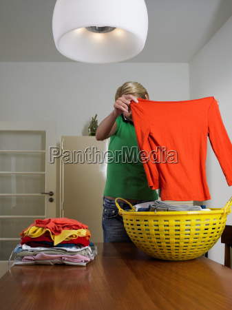 woman folding clothes whilst on mobile