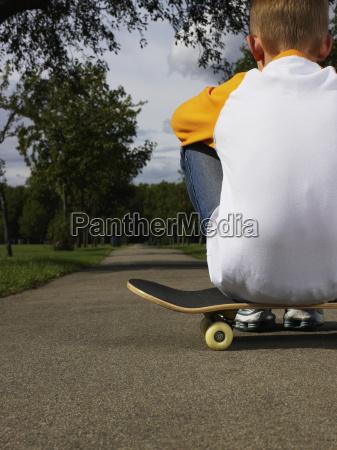 boy sitting on a skateboard