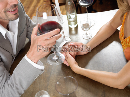 couple holding hands at table