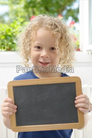 little blond boy holding a chalkboard