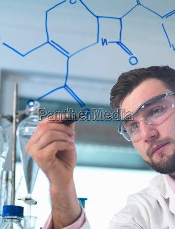 male scientist illustrating antibiotic chemical formula